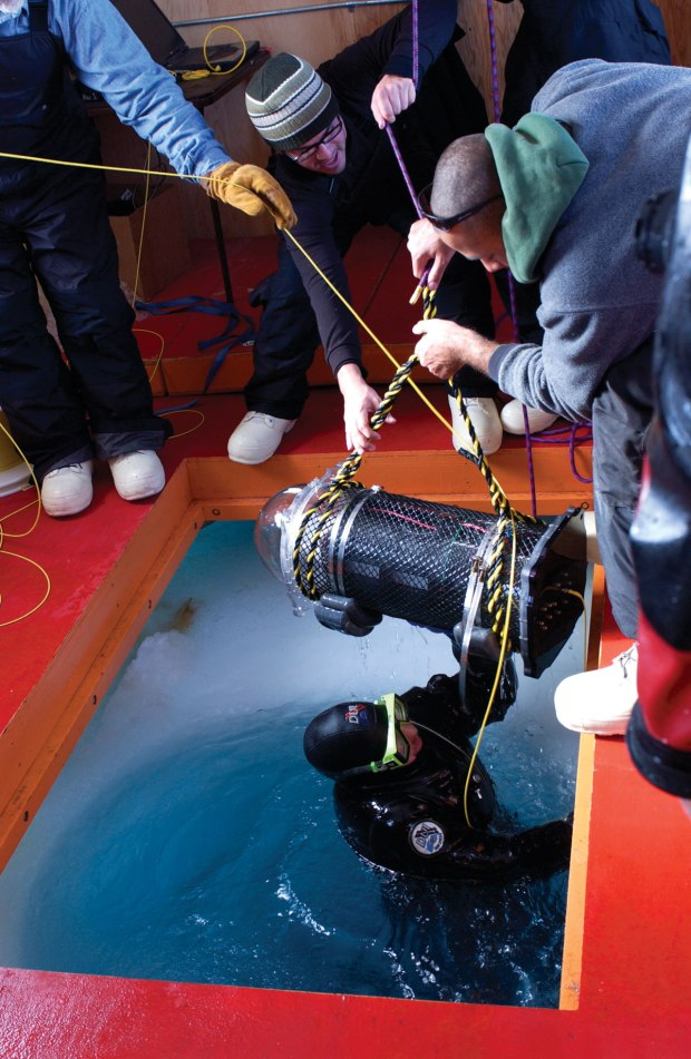 The ROMEO underwater observatory being sent with a diver through a hole in the ice at Cape Evans, Antarctica, on its shakedown test.
