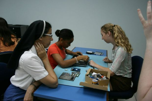 An SJA student helping repair broken computers in Trinidad