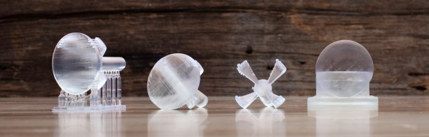 """Left to right: (1) Lens printed with supports in clear resin with 50 micron layers. """"Housing"""" connected to lens with 12 x 1mm thick posts has 6mm rod to fit into cordless drill. (2) Convex side of lens polished. (3) Housing removed. (4) Press fit housing to polish flat side of lens."""