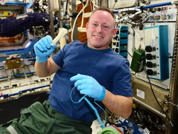 """ISS Commander Barry """"Butch"""" Wilmore holds up the ratcheting socket wrench on the space station right after it was 3D-printed it (Credit: NASA)."""
