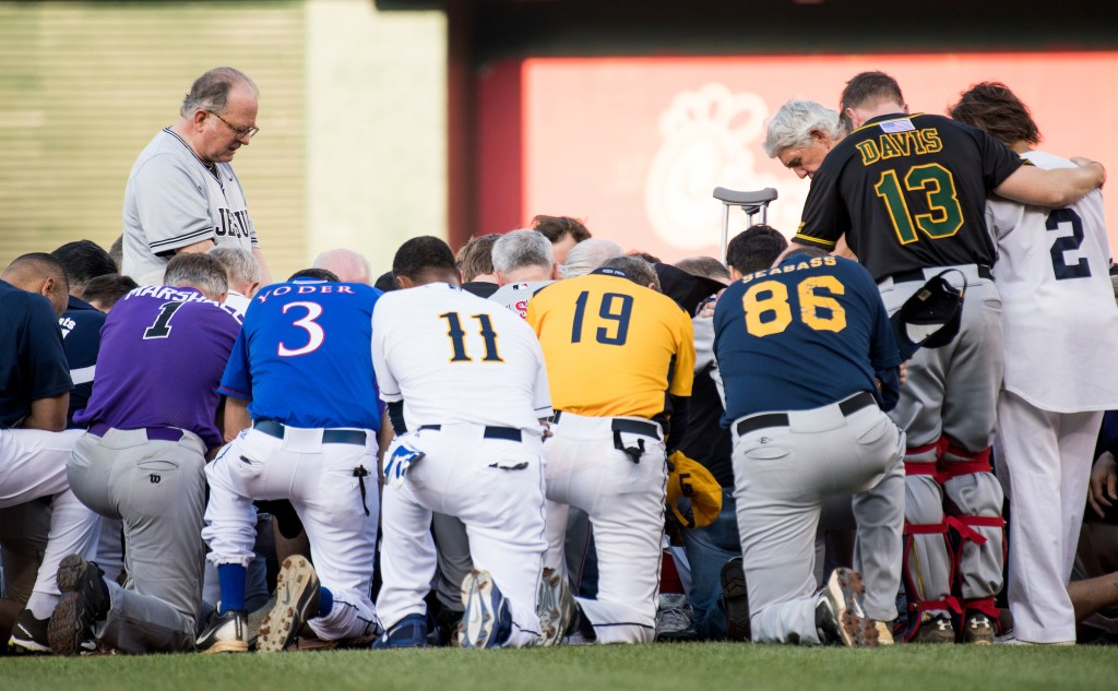 Patrick Conroy, Chaplain of the House of Representatives, left, leads both teams in a moment of prayer before the start of the game. (Bill Clark/CQ Roll Call)