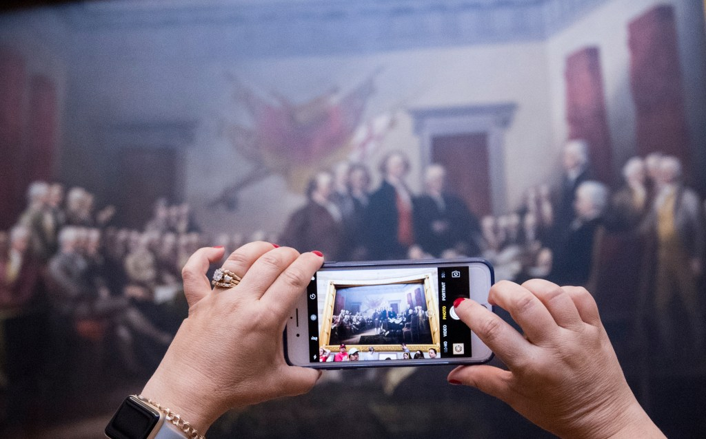 A tourist takes a photo of the painting on Wednesday. (Bill Clark/CQ Roll Call)