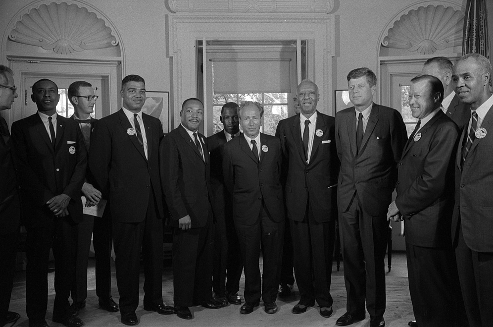 Civil rights leaders, — including John Lewis, center, and Rev. Martin Luther King (center left) — meet with President John F. Kennedy in the Oval Office after the March on Washington on Aug. 28, 1963. From left to right: Willard Wirtz (Secretary of Labor); Floyd McKissick (CORE); Mathew Ahmann (National Catholic Conference for Interracial Justice); Whitney Young (National Urban Leage); Martin Luther King, Jr.(SCLC); John Lewis (SNCC); Rabbi Joachim Prinz (American Jewish Congress); A. Philip Randolph, with Reverend Eugene Carson Blake partially visible behind him; President John F. Kennedy; Walter Reuther (labor leader), with Vice President Lyndon Johnson partially visible behind him; and Roy Wilkins (NAACP). (Photo by Warren K. Leffler, courtesy the Library of Congress Prints and Photographs Division.)