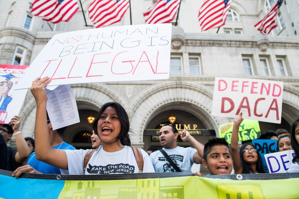 Immigration rights demonstrators hold signs in front of the Trump International Hotel in Washington to oppose President Trump's decision to end the DACA program for