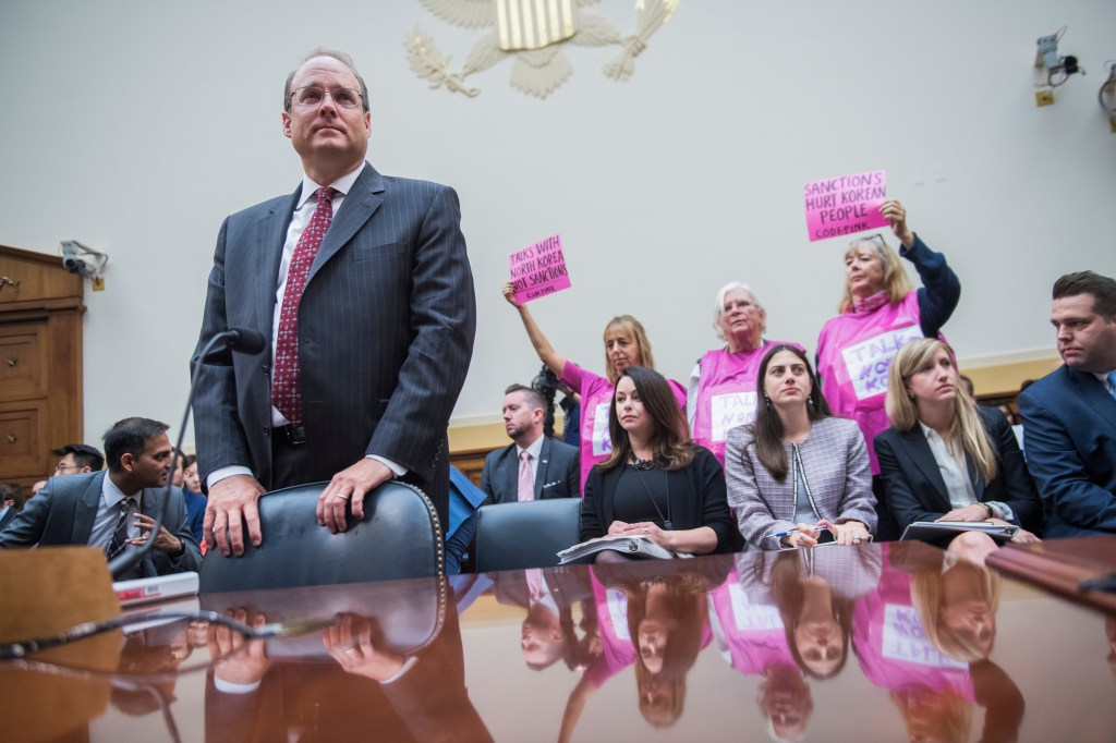 UNITED STATES - SEPTEMBER 12: Marshall Billingslea, Assistant Secretary of State for Terrorist Financing, prepares to testify during a House Foreign Affairs Committee hearing on sanctions and diplomacy with North Korea on September 12, 2017. Members of Code Pink hold signs opposing sanctions on North Korea. (Photo By Tom Williams/CQ Roll Call)