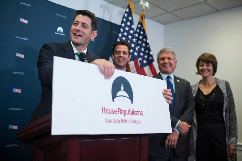 UNITED STATES - SEPTEMBER 13: Speaker of the House Paul Ryan, R-Wis., fixes a sign that was bumped by a photographer as Reps. Tom Graves, R-Ga., Michael McCaul, R-Texas, and Conference Chair Cathy McMorris Rodgers, R-Wash., look on, during a news conference in the Capitol after a meeting of House Republican Conference on September 13, 2017. (Photo By Tom Williams/CQ Roll Call)