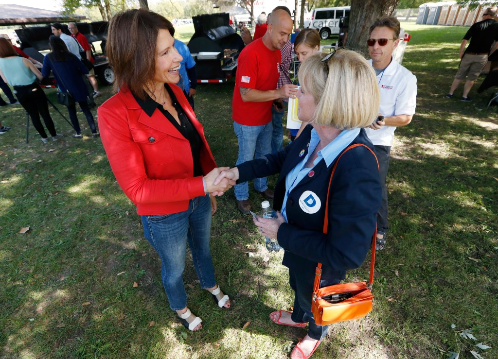 U.S. Rep. Cheri Bustos, D-Ill., left, talks with Iowa gubernatorial candidate Cathy Glasson during the Polk County Democrats Steak Fry, Saturday, Sept. 30, 2017, in Des Moines, Iowa. (AP Photo/Charlie Neibergall)