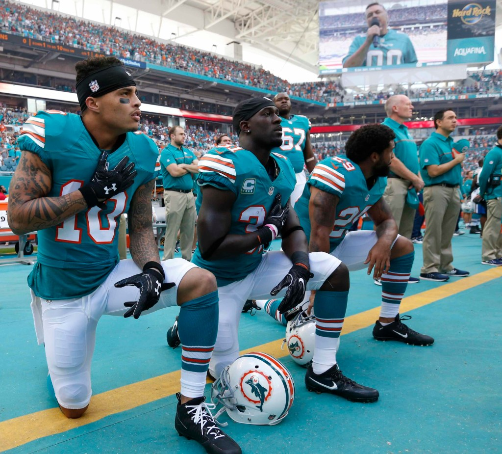 In this Sunday, Oct. 23, 2016, photo, Miami Dolphins wide receiver Kenny Stills (10), free safety Michael Thomas (31) and defensive back Chris Culliver (29) kneel during the National Anthem before the first half of an NFL football game against the Buffalo Bills in Miami Gardens, Fla. At least one website blamed Dolphins cornerback Byron Maxwell for getting burned last week on a 67-yard touchdown pass to the Buffalo Bills' Marquise Goodwin. Soon after the game, safety Thomas took to Twitter to take the blame. (AP Photo/Wilfredo Lee)