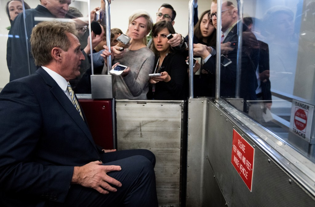 Sen. Jeff Flake, R-Ariz., boards the Senate subway as reporters ask questions on Tuesday, Feb. 13, 2018. (Photo By Bill Clark/CQ Roll Call)