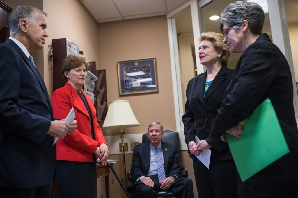 UNITED STATES - FEBRUARY 07: From left, Sens. Them Tillis, R-N.C., Jeanne Shaheen, D-N.H., Johnny Isakson, R-Ga., Debbie Stabenow, D-Mich., and Joni Ernst, R-Iowa, prepare for a news conference in the Capitol on February 7, 2018, to announce a bipartisan resolution to form a Senate committee to investigate USA Gymnastics and the U.S. Olympic Committee on the handling of Larry Nassar and his sexual abuse of athletes. (Photo By Tom Williams/CQ Roll Call)