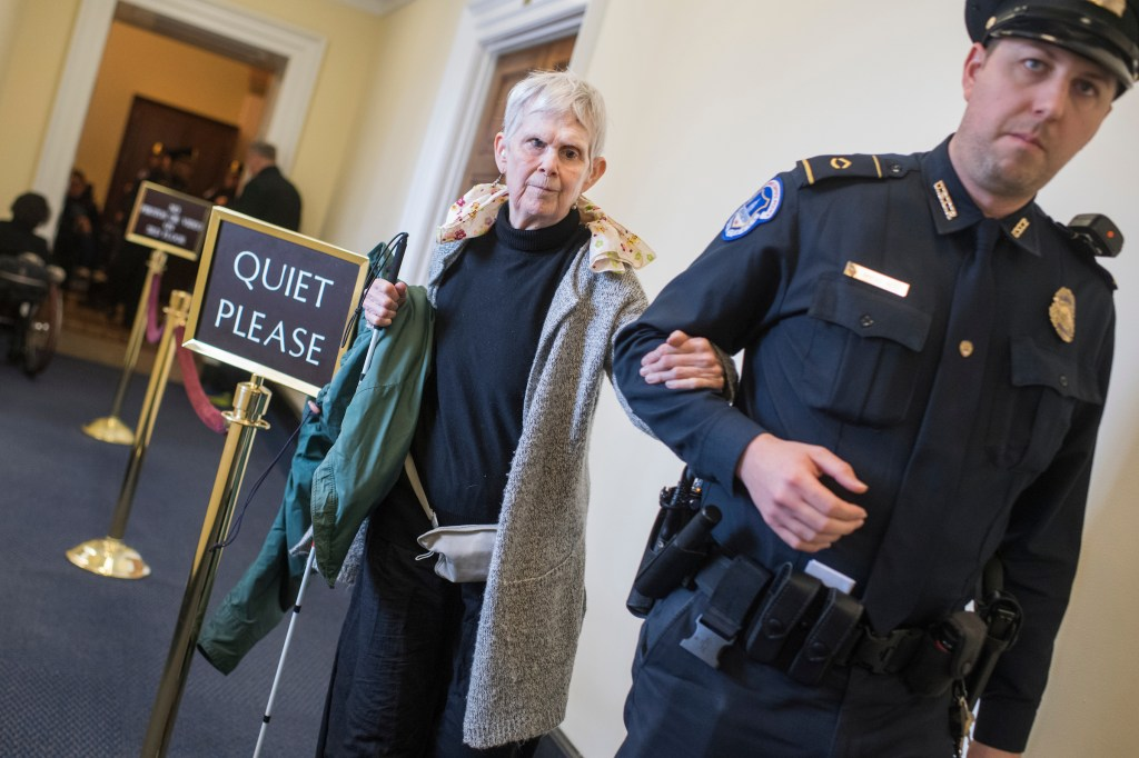 Harriotte Ranvig, 71, of Somerville Mass., is escorted out of the House chamber on February 15, 2018, after she and a group of protesters disrupted the vote on The ADA Education and Reform Act on which makes it harder for disabled people to sue for discrimination. (Tom Williams/CQ Roll Call)