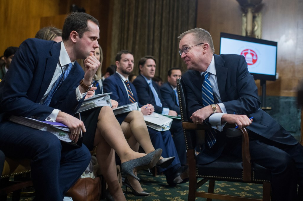 Mick Mulvaney, right, director of the Office of Management and Budget, talks with aide Jonny Slemrod during a Senate Budget Committee hearing on the