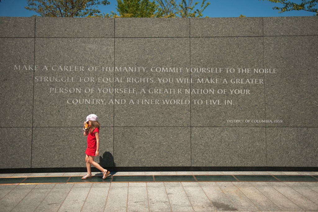 UNITED STATES - AUGUST 23: A child walks past a quotation by Martin Luther King Jr., on the site of the memorial dedicated to the civil rights leader. The memorial, located on the Tidal Basin, is open to viewing by the public and the official dedication ceremony will take place on August 28. (Photo By Tom Williams/Roll Call)