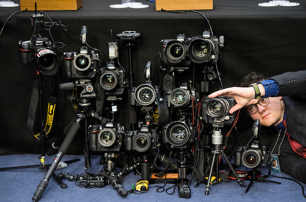 A news photographer sets up a remote camera in the well of the hearing room before the start of the Senate Commerce, Science and Transportation Committee and Senate Judiciary Committee joint hearing on