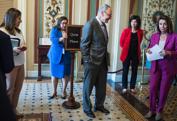 Senate Minority Leader Charles Schumer, D-N.Y., Lily Eskelsen Garcia, in red, president of the National Education Association, and House Minority Leader Nancy Pelosi, D-Calif., right, prepare for a news conference in the Capitol to announce part of the Democrats'