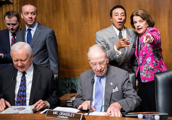 Sen. Dianne Feinstein, D-Calif., points recording artist Smokey Robinson to his seat at the witness table as Sen. Orrin Hatch, R-Utah, and Sen. Chuck Grassley, R-Iowa, take their seats before the start of the Senate Judiciary Committee hearing on