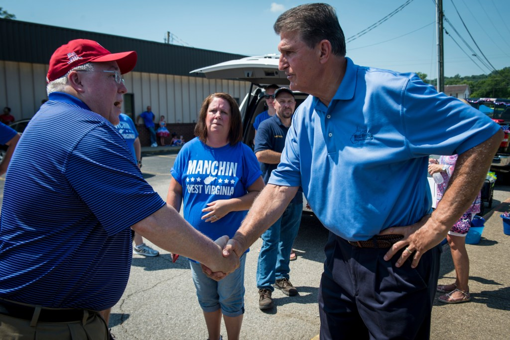 UNITED STATES - July 4: Sen. Joe Manchin, R-W.Va., shakes hands with Attorney General Patrick Morrisey, who is also running for U.S. Senate, before the start of the Ripley 4th of July Grand Parade in Ripley, West Virginia Wednesday July 4, 2018. (Photo By Sarah Silbiger/CQ Roll Call)
