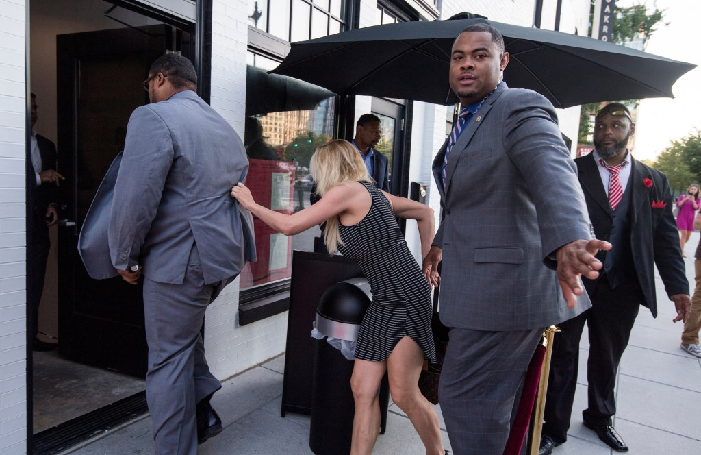 Stephanie Clifford, also known as adult film star and director Stormy Daniels, arrives for her first night of a two-night appearance surrounded by security at The Cloakroom strip club in Washington on Monday, July 9, 2018. (Bill Clark/CQ Roll Call file photo)