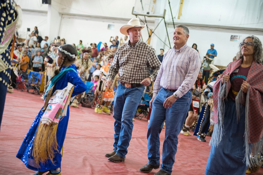 """""""Don't walk. Dance. Dance."""" Those were the orders two weeks ago at Crow Fair in Montana, where GOP Rep. Greg Gianforte, center left, and his Democratic opponent, former state Rep. Kathleen Williams marched in the grand entry together. Arkansas Rep. Bruce Westerman was just along for the ride. (Tom Williams/CQ Roll Call)"""