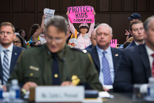 Protesters with children attempt to interrupt the opening statement of Carla L. Provost, foreground, acting chief of the U.S. Border Patrol, during a Senate Judiciary Committee hearing in Hart Building titled