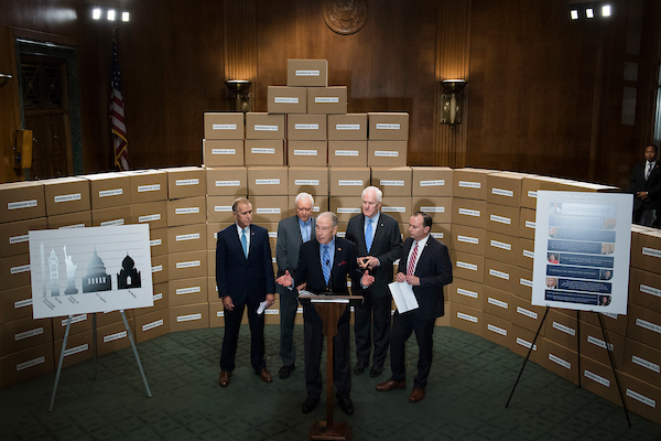 UNITED STATES - AUGUST 02: From left, Sens. Thom Tillis, R-N.C., Orrin Hatch, R-Utah, Senate Judiciary Committee Chairman Charles Grassley, R-Iowa, John Cornyn, R-Texas, and Mike Lee, R-Utah, conduct a news conference in Dirksen Building on August 2, 2018, with boxes representing roughly 1 million pages of documents to be submitted to the committee on Supreme Court nominee Brett Kavanaugh. (Photo By Tom Williams/CQ Roll Call)