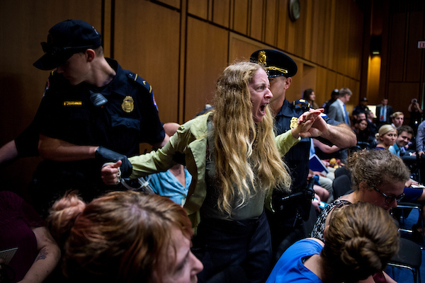 UNITED STATES – SEPT 4: A protester is removed by Capitol police during the hearing of Supreme Court nominee Brett Kavanaugh in front of the Senate Judiciary Committee in the Hart Senate Office Building Tuesday Sept. 4, 2018. (Photo By Sarah Silbiger/CQ Roll Call)