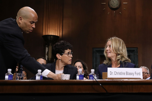 Senate Judiciary Committee member Sen. Cory Booker, D-N.J., delivers coffee to Blasey Ford as she testifies. (POOL Photo by Win McNamee/Getty Images)