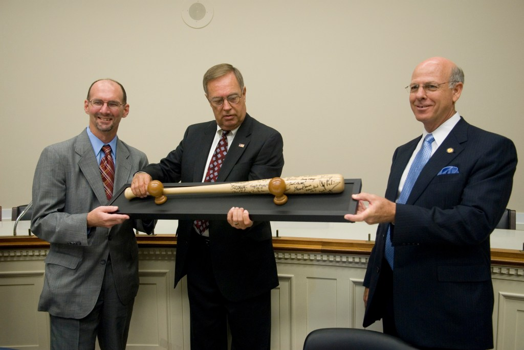 Rep. Mike Oxley, center, presents his legislative director, Tim Johnson, with a team-signed bat and a check as Rep. Steve Pearce, right, looks on in the Rayburn Building. The $5000 check, donated by Aramark fom their concession stand sales, was for the Multiple Myeloma Research Foundation.