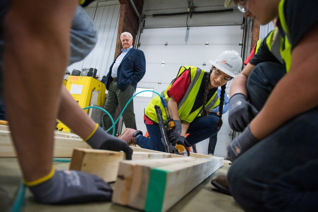 UNITED STATES - SEPTEMBER 20: Rep. Collin Peterson, D-Minn., observes Destiny Stockland use a nail gun, during a program for high schoolers that teaches them a skill, including carpentry, at Marcus Construction in Willmar, Minn., on September 20, 2018. (Photo By Tom Williams/CQ Roll Call)