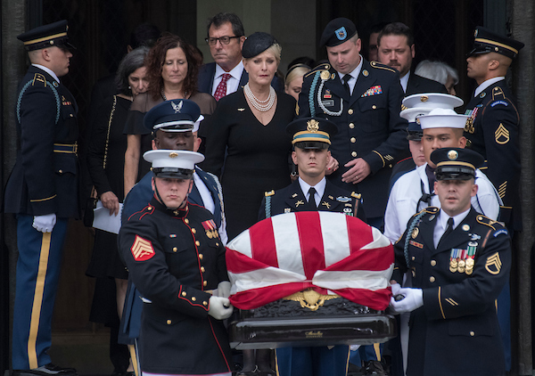 UNITED STATES - SEPTEMBER 1: Cindy McCain, the wife of the late Sen. John McCain, R-Ariz., and their son, Jimmy, follow an Honor Guard carrying his casket out of the Washington National Cathedral after his funeral on September 1, 2018. (Photo By Tom Williams/CQ Roll Call)