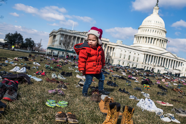 UNITED STATES - MARCH 13: Evelyn Black, 2 1/2, of Capitol Hill, walks through about 7000 pairs of shoes that are displayed on the east lawn of the Capitol on March 13, 2018, to represent the 7000 children who were killed by guns since the Sandy Hook shooting in 2012. (Photo By Tom Williams/CQ Roll Call)