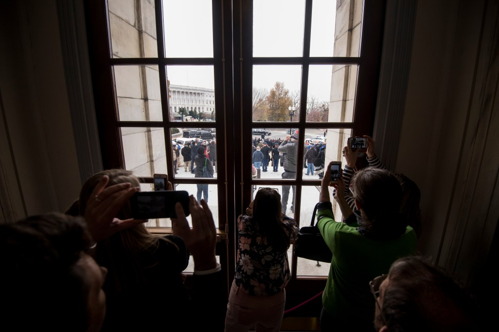 UNITED STATES - DECEMBER 5: Senate staffers watch from inside the Russell Senate Office Building as the funeral procession for former President George H.W. Bush departs the Capitol on Wednesday morning, Dec. 5, 2018. (Photo By Bill Clark/CQ Roll Call)