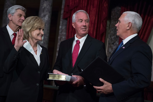 Sen. Cindy Hyde-Smith, R-Miss., participates in her swearing-in ceremony in the Capitol's Old Senate Chamber with Vice President Mike Pence, right, and her husband Michael, after being sworn in on the Senate floor on April 9, 2018. Mississippi Gov. Phil Bryant appears at left. (Tom Williams/CQ Roll Call)