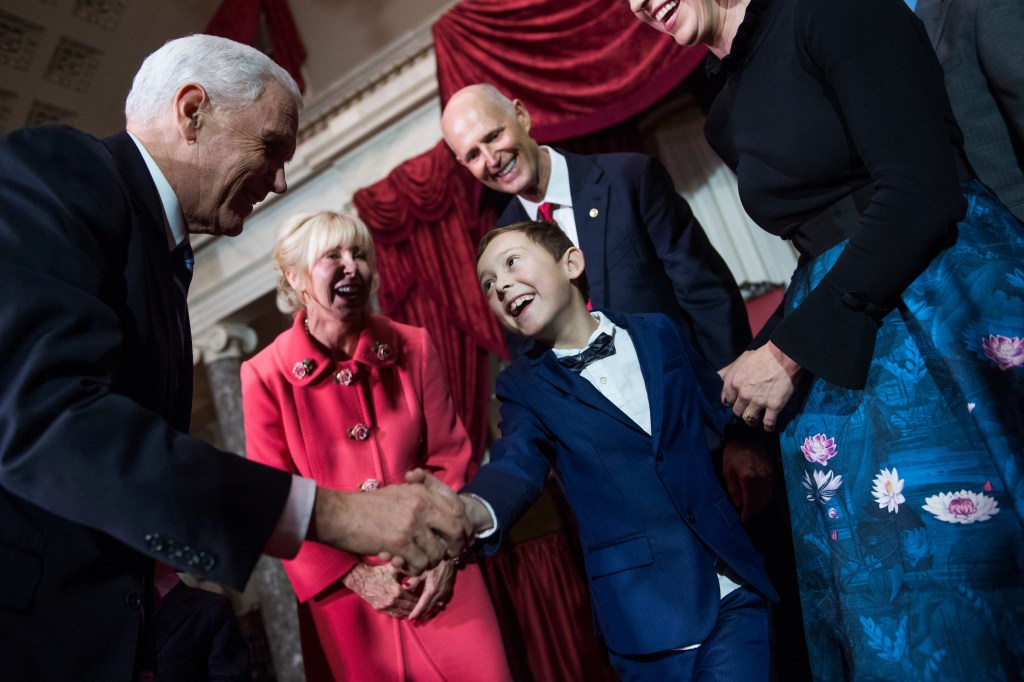 UNITED STATES - JANUARY 08: The grandson of Sen. Rick Scott, R-Fla., Auguste, greets Vice President Mike Pence as Scott and his wife, Ann, look on, during a swearing-in ceremony in the Capitol's Old Senate Chamber after Scott was sworn in on the Senate floor the on January 8, 2019. (Photo By Tom Williams/CQ Roll Call)