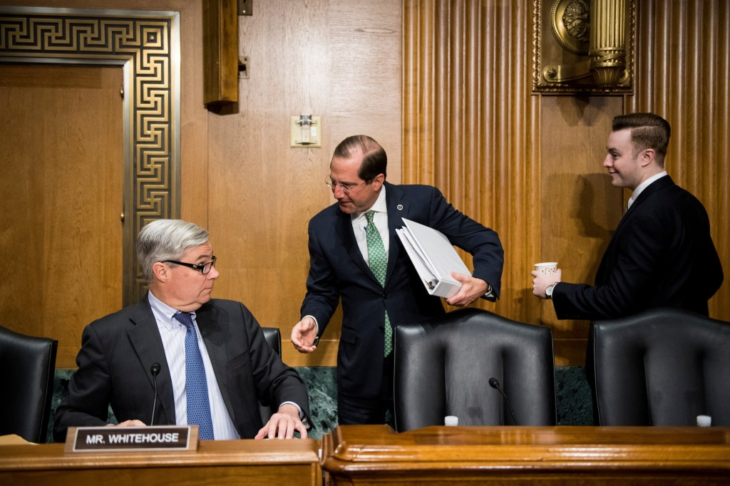 Secretary of Health and Human Services Alex Azar, center, speaks with Sen. Sheldon Whitehouse, D-R.I., before the start of the Senate Finance Committee hearing on