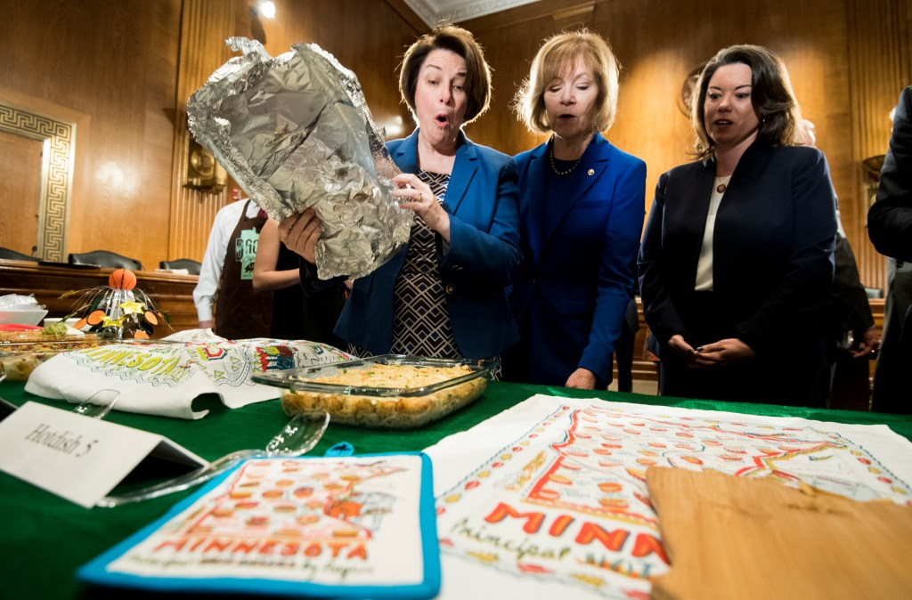 UNITED STATES - APRIL 9: From left, Sen. Amy Klobuchar, D-Minn., Sen. Tina Smith, D-Minn., and Rep. Angie Craig, D-Minn., react as the uncover hot dish entries at the annual Minnesota Congressional Delegation Hotdish Competition on Tuesday, April 9, 2019. (Photo By Bill Clark/CQ Roll Call)