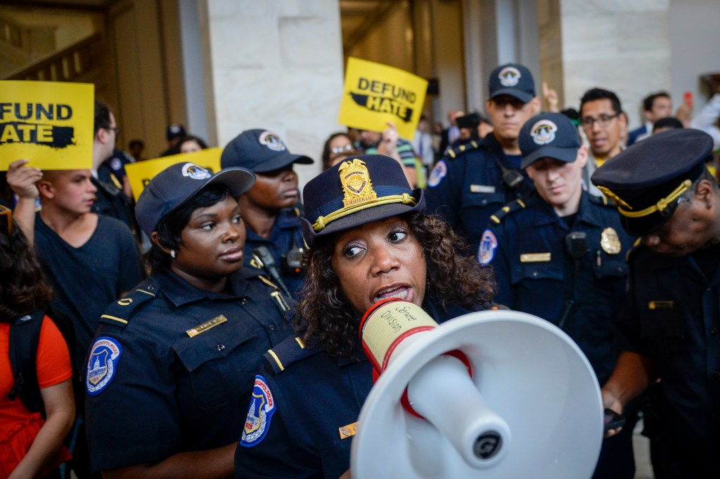 UNITED STATES - JUNE 25: U.S. Capitol Police give a warning to the Defund Hate campaign to leave the area as it holds a protest in the Russell Rotunda to honor immigrants who died in ICE and CBP detention on Tuesday June 25, 2019. (Photo by Caroline Brehman/CQ Roll Call)
