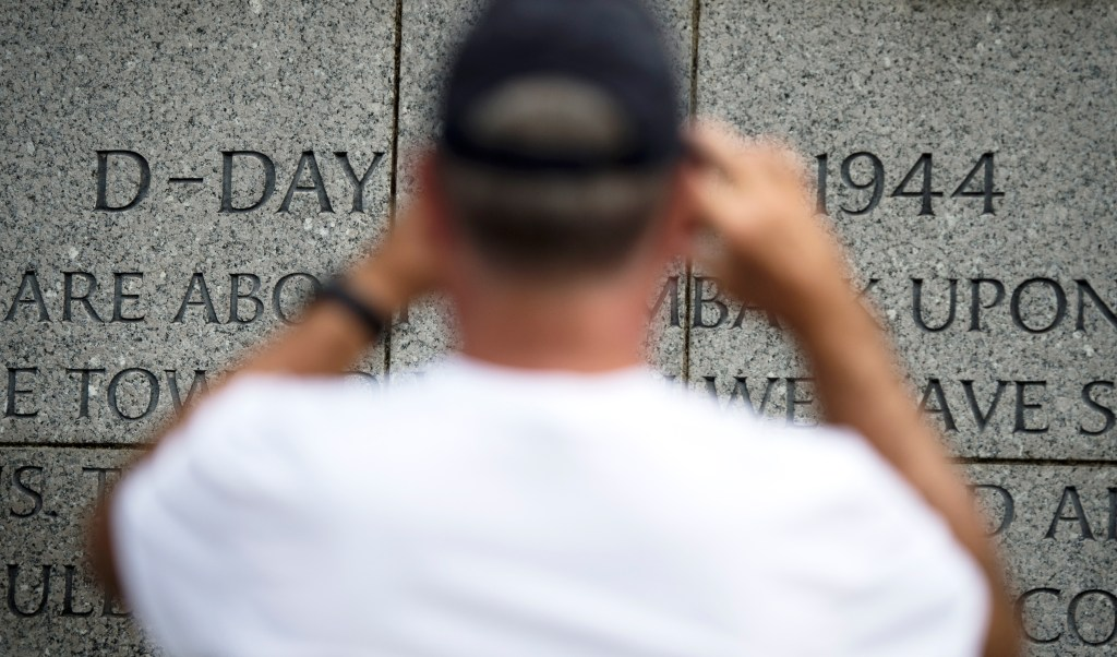 UNITED STATES - JUNE 5: A man takes a cell phone photo of a message about D-Day engraved on a wall at the World War II Memorial in Washington on Wednesday June 5, 2019. (Photo by Caroline Brehman/CQ Roll Call)