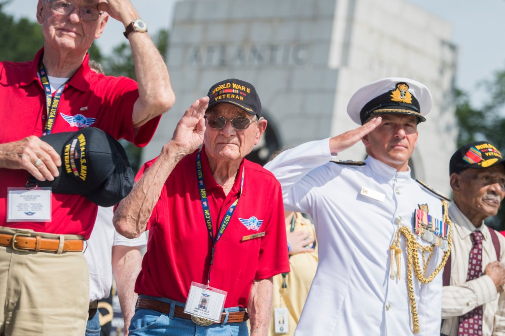 UNITED STATES - JUNE 6: World War II Navy veteran James Keele, second from left, 93, of New Mexico, who landed on the Normandy beaches on D-Day, salutes during a ceremony at the National World War II Memorial to commemorate the 75th anniversary of invasion on Thursday, June 6, 2019. Keele was part of an Honor Flight group from New Mexico. (Photo By Tom Williams/CQ Roll Call)