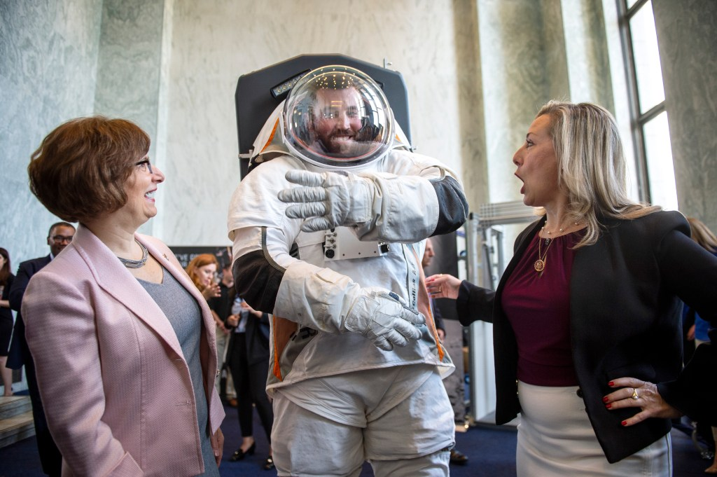 UNITED STATES - JULY 25: Rep. Suzanne Bonamici, D-Ore., left, and Space Subcommittee Chair Rep. Kendra Horn, D-Okla., talk with a man modeling a possible prototype of the future suit for the upcoming mission to the moon in the Rayburn Building in Washington on Thursday July 25, 2019. (Photo by Caroline Brehman/CQ Roll Call)