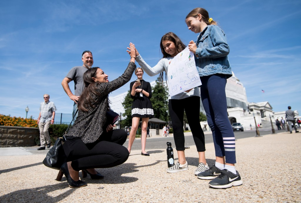 UNITED STATES - SEPTEMBER 20: Rep. Alexandria Ocasio-Cortez, D-N.Y., high-fives climate striking students Evelyn Seek, center, and Pema Duncan, right, as they hold their climate strike sign in front of the Capitol on Friday, Sept. 20, 2019. (Photo By Bill Clark/CQ Roll Call)