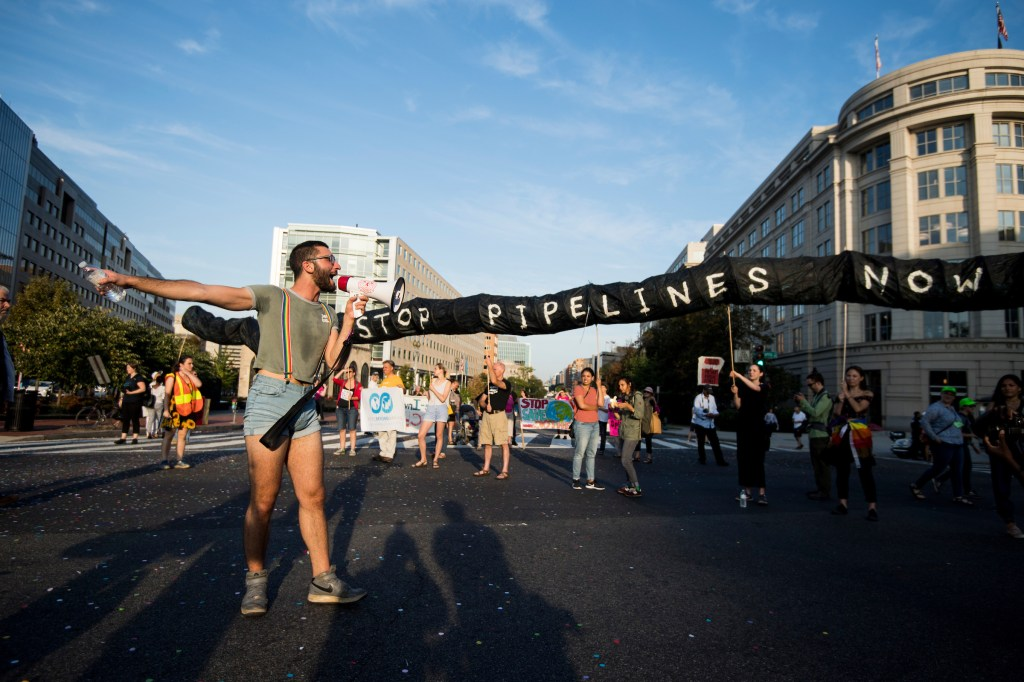 "UNITED STATES - SEPTEMBER 23: Firas Nasr uses a megaphone to guide protesters to the next intersection as cllimate change protesters block the intersection of Massachusetts Avenue and North Capitol Street near the U.S. Capitol at rush hour on Monday, Sept. 23, 2019. A coalition of climate activists under the umbrella ""Shut Down D.C."" blocked intersections throughout DC to draw attention to climate change. (Photo By Bill Clark/CQ Roll Call)"