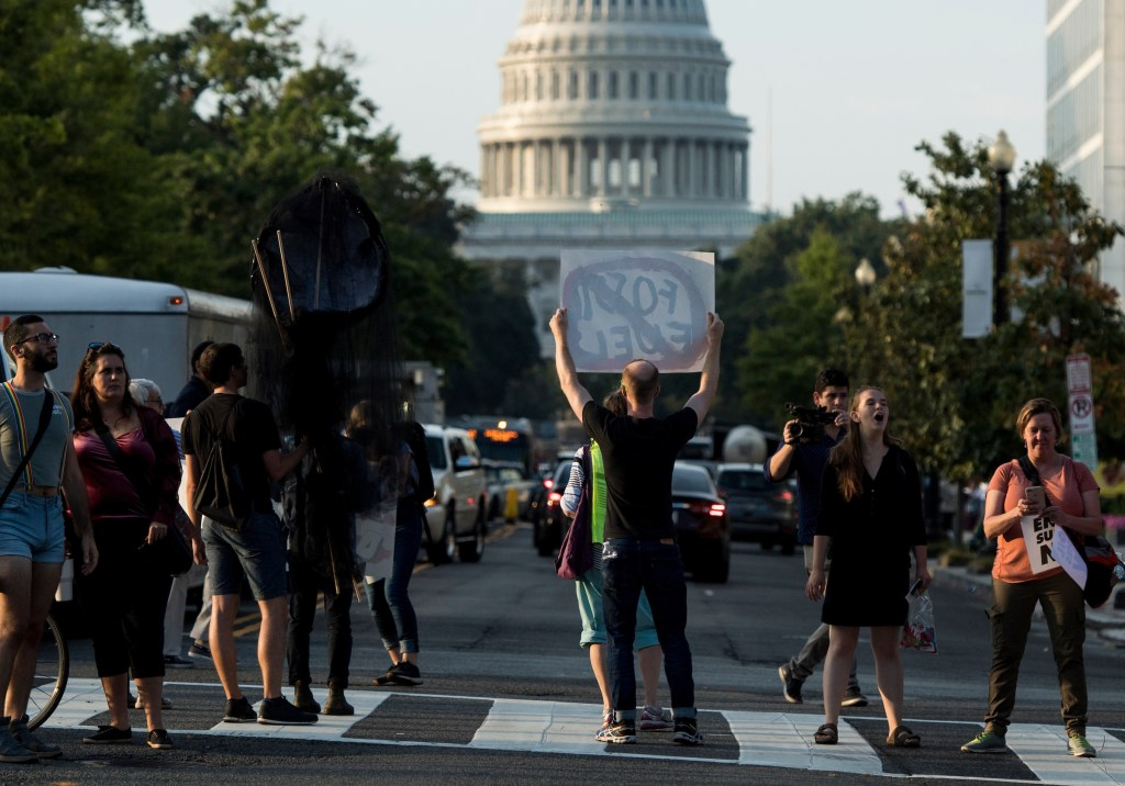 """UNITED STATES - SEPTEMBER 23: Climate change protesters block the intersection of Massachusetts Avenue and North Capitol Street near the U.S. Capitol at rush hour on Monday, Sept. 23, 2019. A coalition of climate activists under the umbrella """"Shut Down D.C."""" blocked intersections throughout DC to draw attention to climate change. (Photo By Bill Clark/CQ Roll Call)"""