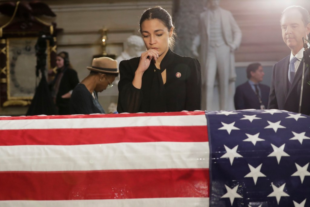 WASHINGTON, DC - OCTOBER 24: U.S. Rep. Alexandria Ocasio-Cortez (D-NY) stops to pay her respects over the flag-draped casket of U.S. Rep. Elijah Cummings (D-MD) in National Statuary Hall at the U.S. Capitol during a memorial service October 24, 2019 in Washington, DC. Rep. Cummings passed away on October 17, 2019 at the age of 68 from
