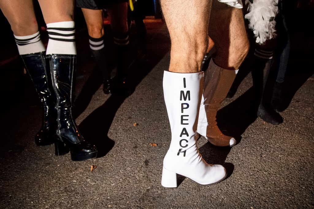 "UNITED STATES - OCTOBER 29: A man dressed as a whistleblower wears boots that read ""impeach"" as he participates in the costume parade before the start of the 33rd Annual 17th Street High Heel Race on Tuesday Oct. 29, 2019. (Photo by Caroline Brehman/CQ Roll Call)"
