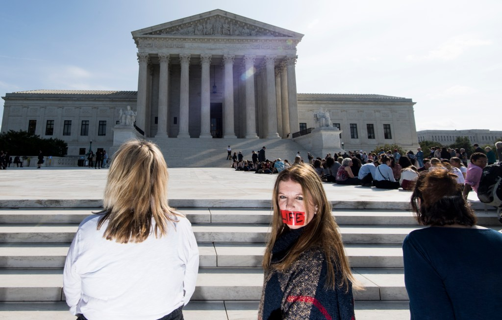 UNITED STATES - OCTOBER 7: Pro-life abortion protesters, with red tape over their mouths, stand in silent protest on the first day of the new session of the U.S. Supreme Court on Monday, Oct. 7, 2019. (Photo By Bill Clark/CQ Roll Call)
