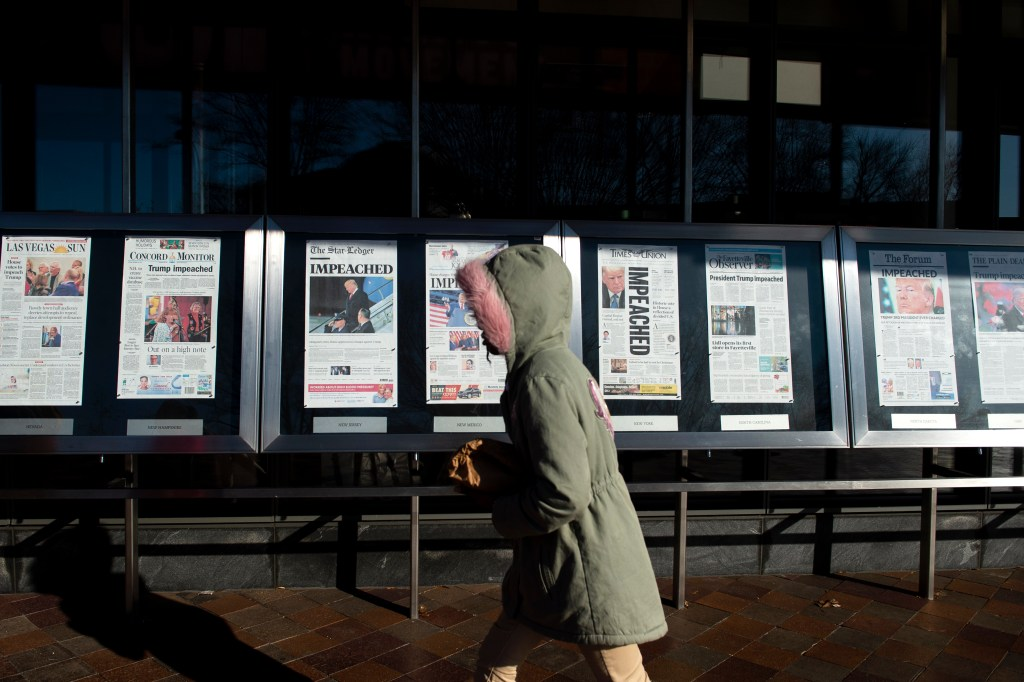 UNITED STATES - DECEMBER 19: A person walks by the newspaper front pages, from around the US, on display at the Newseum the day after the House of Representatives passed two articles of impeachment against President Donald Trump on Thursday Dec. 19, 2019. (Photo by Caroline Brehman/CQ Roll Call)