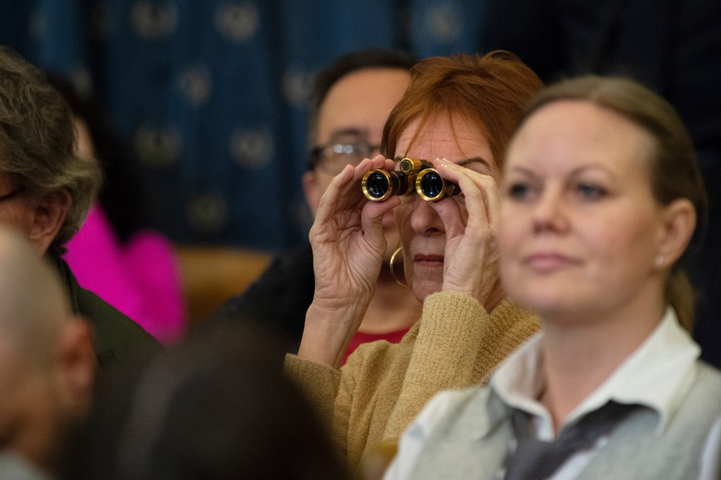 2020 vision?: A spectator uses binoculars Wednesday to watch the House Judiciary impeachment hearing. (Caroline Brehman/CQ Roll Call)