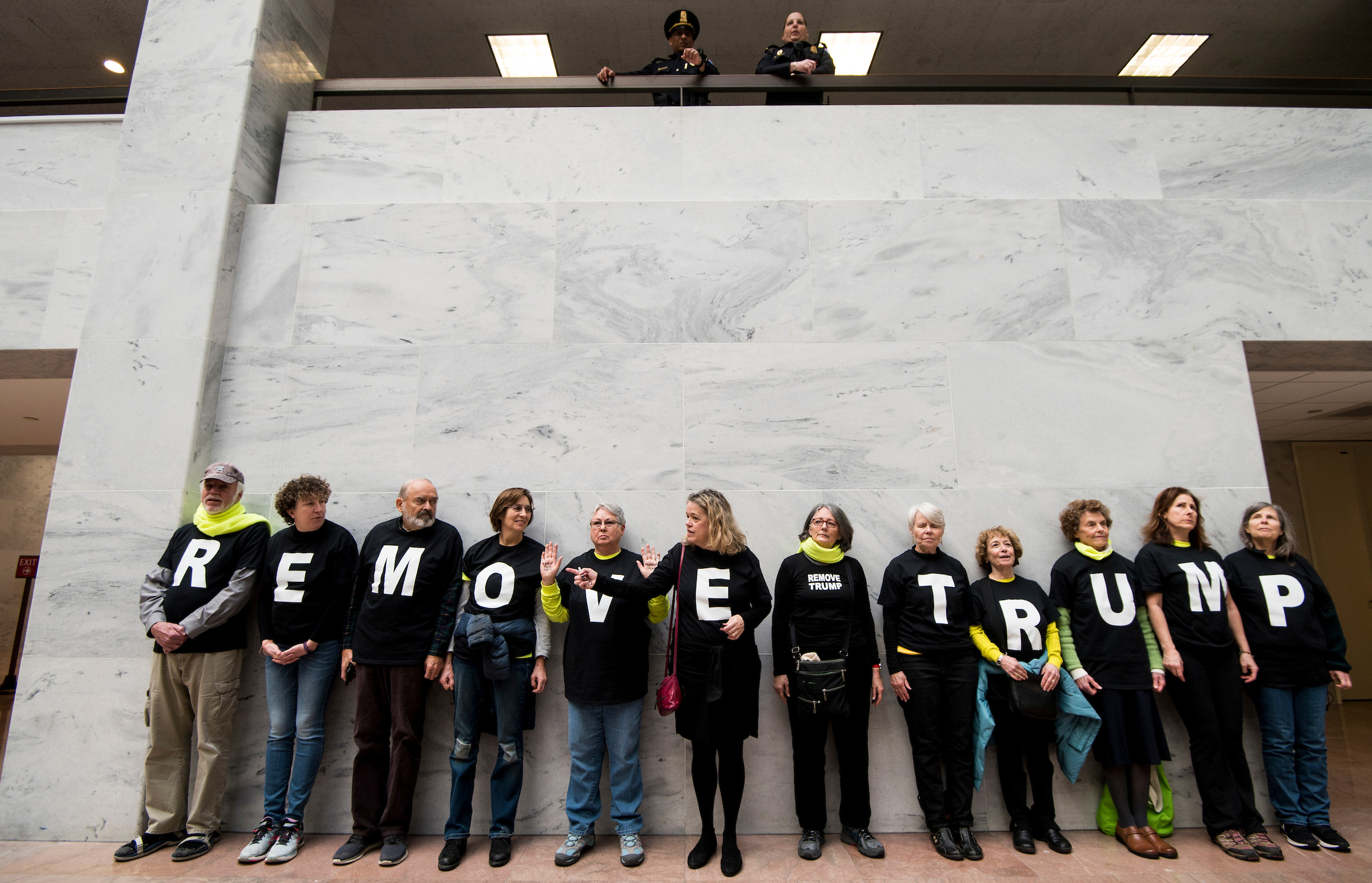 """Protesters participate in the """"Swarm the Senate"""" rally in the Hart Senate Office Building urging action to """"impeach, remove, indict and jail"""" President Trump on Monday. (Bill Clark/CQ Roll Call)"""