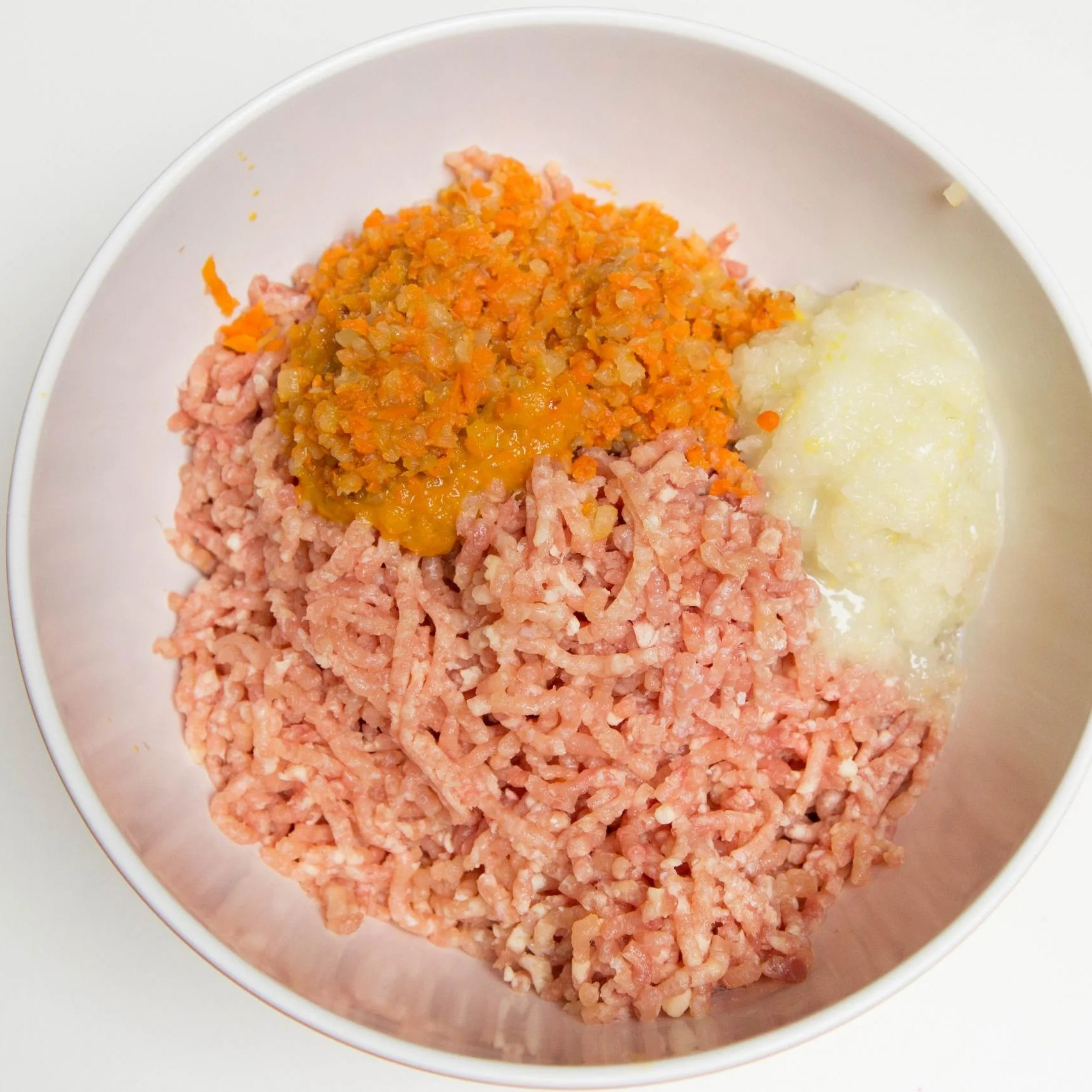 Blended and sautéed carrots and onion and ground chicken in a bowl